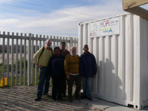 Vorstandsmitglieder von Hope & Future e. V. mit den Gesundheitsarbeitern Karen und Eddie vor dem von uns finanzierten Beratungscontainer in Blikkiesdorp.